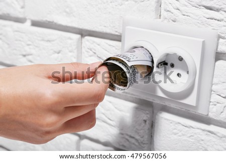 Woman hand putting dollar banknotes into power socket on white wall