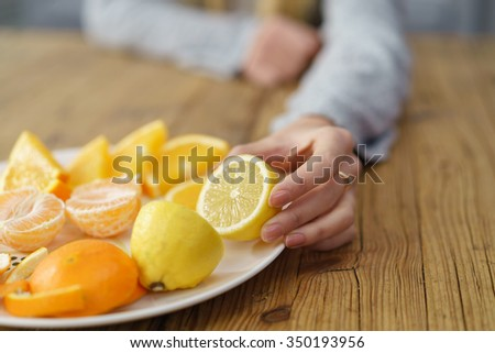 Woman Hand Putting Fresh Healthy Lemon and Orange Fruit on Plate, Placed on top of a Wooden Table. - stock photo