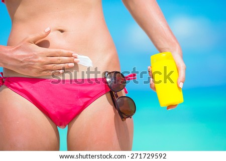 Woman hand putting sunscreen from a suncream bottle - stock photo