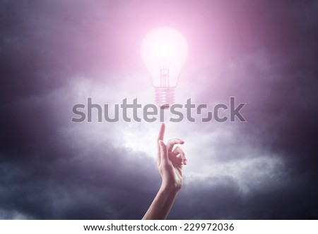 woman hand reaching for magic glowing light bulb over dark sky background - stock photo