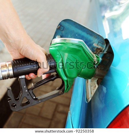 Woman hand refilling the car with fuel on a filling station.