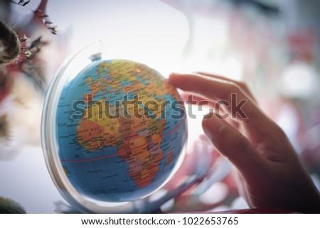 World Map Globe Ball. Woman hand select destination on the world map globe ball  Travel concept vintage color Hand Select Destination On World Stock Photo 1022653765