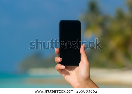 Woman hand showing a blank smart phone on the beach with the sea in the background - stock photo