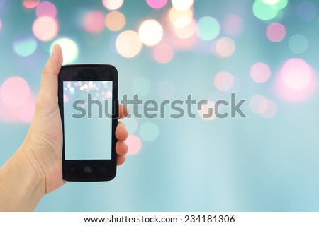 Woman hand showing smart phone with isolated screen on an abstract blurred circular bokeh lights background - stock photo