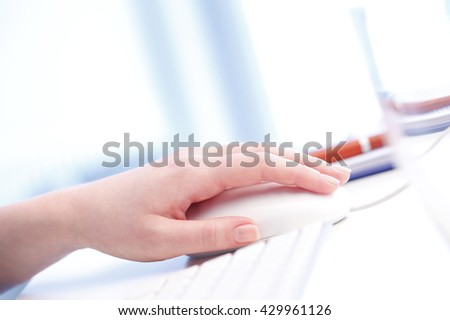 Woman hand touching computer mouse and typing on keyboard while working online at office.