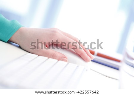 Woman hand touching computer mouse while working online at office.