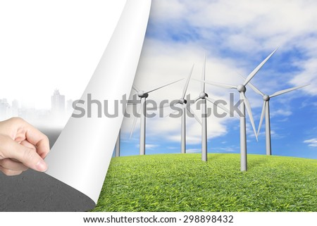 Woman hand turning gray cityscape page revealing group of wind turbines, alternative energy concept. - stock photo