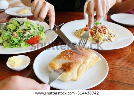 woman hand use knife and fork cut bread on salad table, big meal dinner