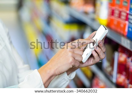 Woman hand using smartphone in supermarket - stock photo