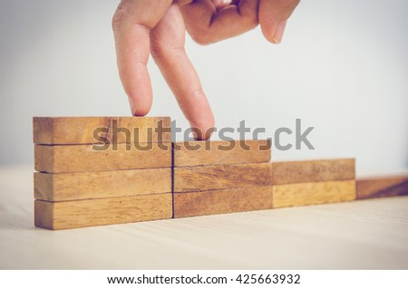 Woman hand walking his fingers up wooden steps on the way to success and aspiration. Business occupation - stock photo