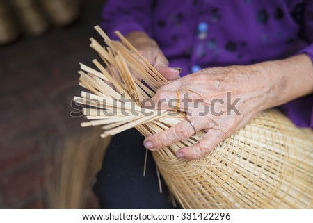 Woman hand weaving tropical bamboo fish trap in traditional crafts village in Vietnam - stock photo