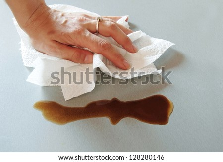 woman hand wiping spilled coffee with paper towel - stock photo