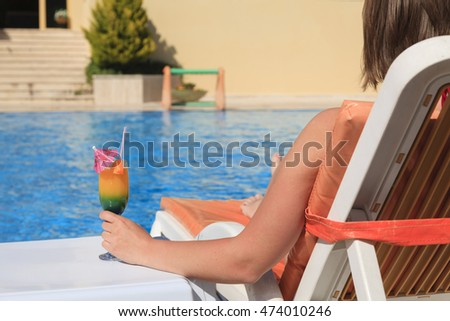 Woman hand with cocktail glass near swimming pool