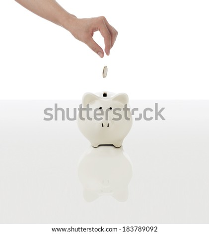 Woman hand with coin and piggy bank.