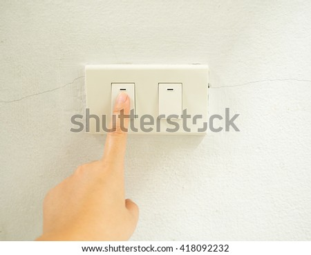 Woman hand with finger on light switch, about to turn off the lights. Closeup of hand and switch only. - stock photo