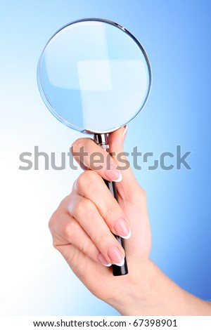 Woman hand with magnifier on blue background - stock photo