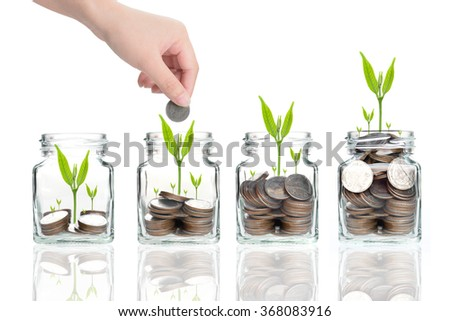 woman hand with money coins in clear bottle on white background,Business investment growth concept,saving concept,Hand putting coins and seed in clear jar over white background - stock photo