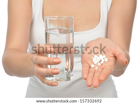 Woman hand with pills medicine tablets and glass of water for headache against white background - stock photo