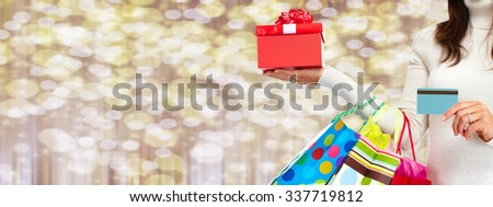 Woman hand with shopping bags over Christmas background. - stock photo