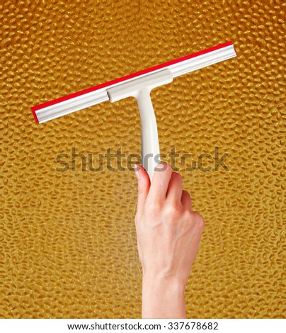 woman hand with special squeegee for cleaning over glass background - stock photo