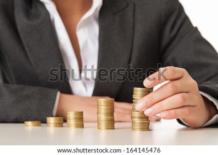 Woman hand with stacks coins against white background  - stock photo