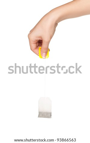 Woman hand with teabag isolated on white background - stock photo