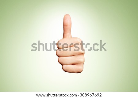 Woman hand with thumb up isolated on green background. Good sign - stock photo