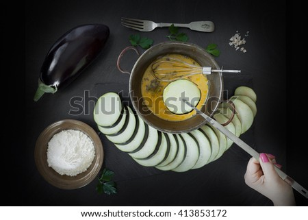 Woman hand with tongs dipping eggplant slice in egg. Fried eggplant preparation, top view shot. - stock photo