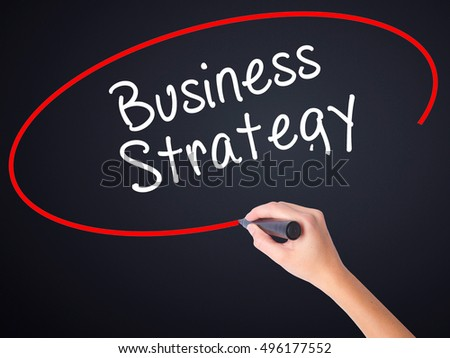 Woman Hand Writing Business Strategy on blank transparent board with a marker isolated over black background. Business concept. Stock Photo