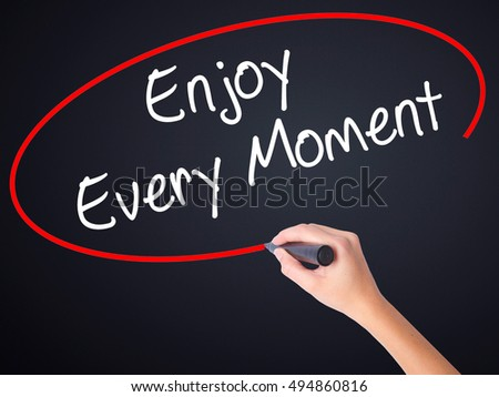 Woman Hand Writing Enjoy Every Moment on blank transparent board with a marker isolated over black background. Stock Photo