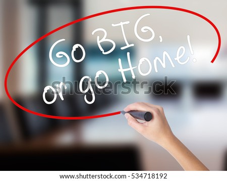 Woman Hand Writing Go Big or Go Home with a marker over transparent board. Isolated on Office. Business concept. Stock Image