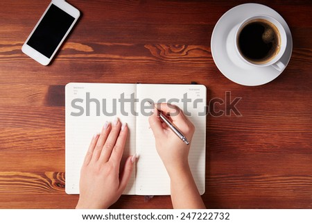 Woman hand writing in a diary, top view - stock photo