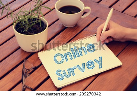 Woman hand writing in notebook Online survey on wooden table with coffee, plant and glasses. Retro colors. - stock photo