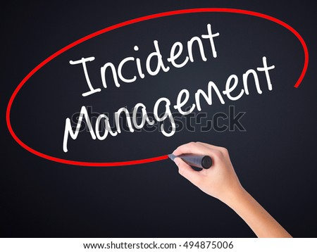 Woman Hand Writing Incident Management on blank transparent board with a marker isolated over black background. Business concept. Stock Photo
