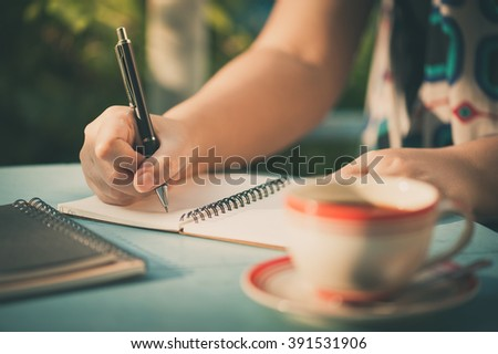 Woman hand writing journal on small notebook at outdoor area in cafe with morning scene and vintage filer effect - stock photo