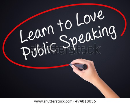 Woman Hand Writing Learn to Love Public Speaking on blank transparent board with a marker isolated over black background. Business concept. Stock Photo