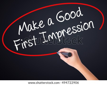 Woman Hand Writing Make a Good First Impression on blank transparent board with a marker isolated over black background. Stock Photo