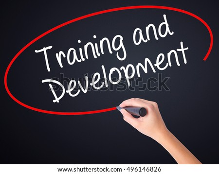 Woman Hand Writing Training and Development on blank transparent board with a marker isolated over black background. Business concept. Stock Photo