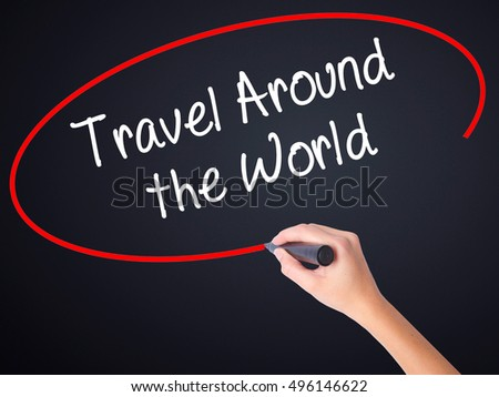 Woman Hand Writing Travel Around the World on blank transparent board with a marker isolated over black background. Business concept. Stock Photo