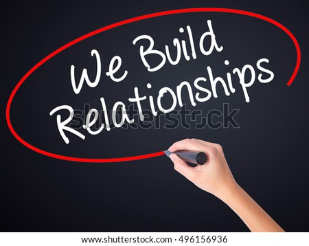 Woman Hand Writing We Build Relationships on blank transparent board with a marker isolated over black background. Business concept. Stock Photo