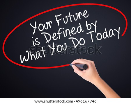 Woman Hand Writing Your Future is Defined by What You Do Today on blank transparent board with a marker isolated over black background. Business concept. Stock Photo