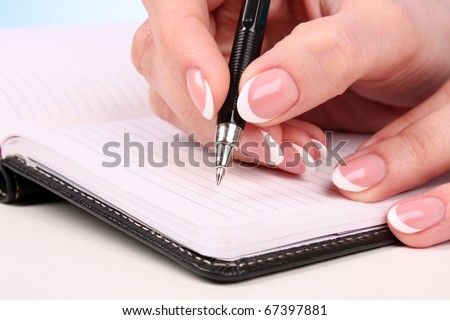 woman hand writting in the notebook on table - stock photo