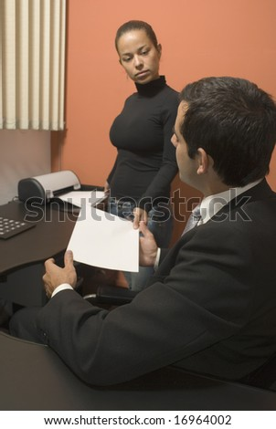 Woman handing businessman paperwork as he sits at his desk. Vertically framed photo. - stock photo