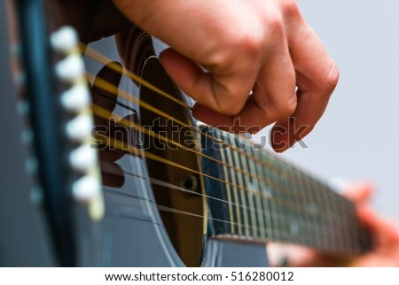 Woman hands and black acoustic guitar. Girl playing guitar.