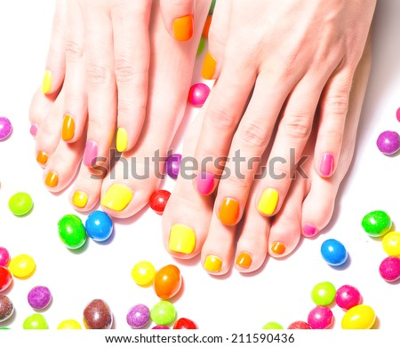 Woman hands and feet with bright candies around - stock photo