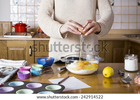 Woman hands breaking an egg to make cupcakes. Woman cooking homemade traditional cupcakes in a rustic kitchen  - stock photo