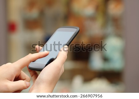 Woman hands buying online with a smart phone in the street in front a store - stock photo