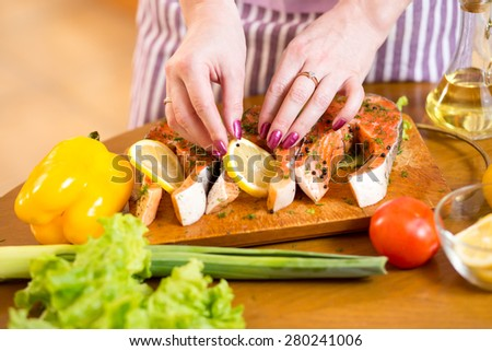 Woman hands cooking trout fish in domestic kitchen