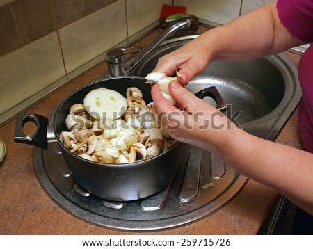 Woman hands cut onions in kettle with mushrooms - stock photo
