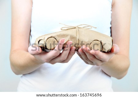 Woman hands holding a car wrapped in brown kraft paper - stock photo